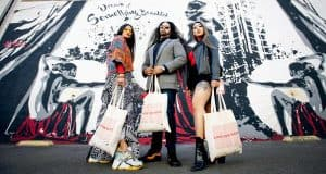 Woman, Man, and Woman standing with tote bags